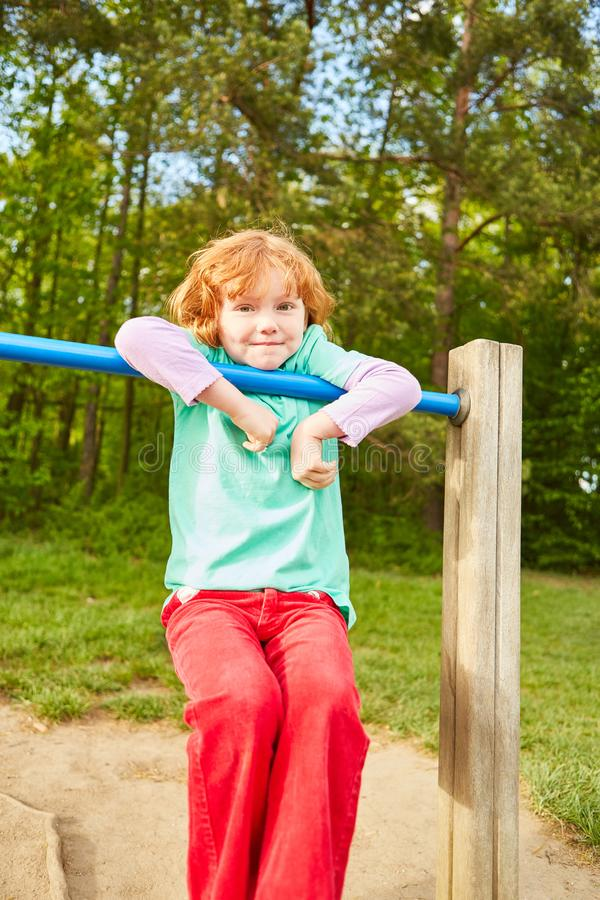 Girl plays and climbs on a jungle gym royalty free stock photo