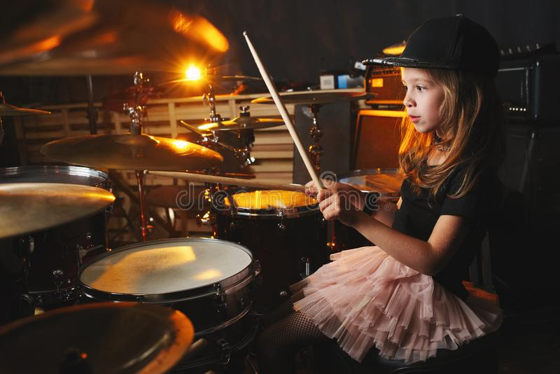 Girl plays drums in recording studio. Little girl plays drums in recording studio stock photography