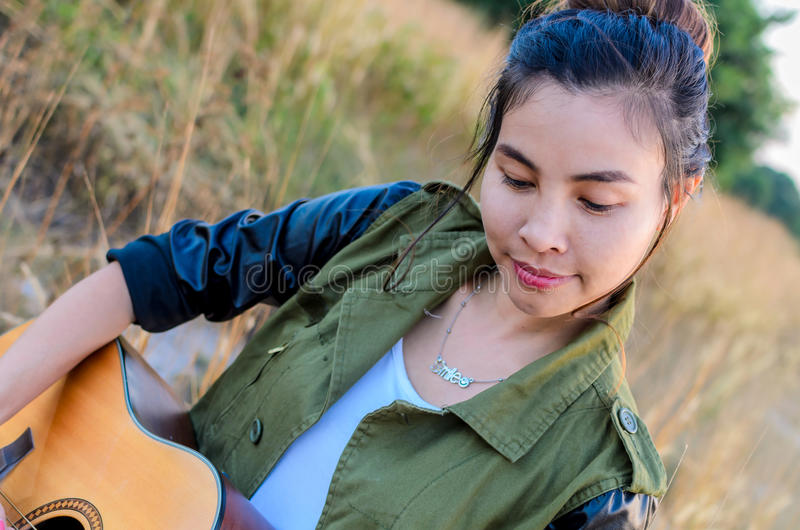 Girl plays guitar in the autumn grass stock images
