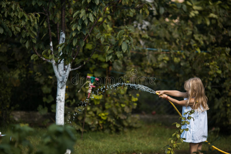 Girl plays with hose in the garden royalty free stock images