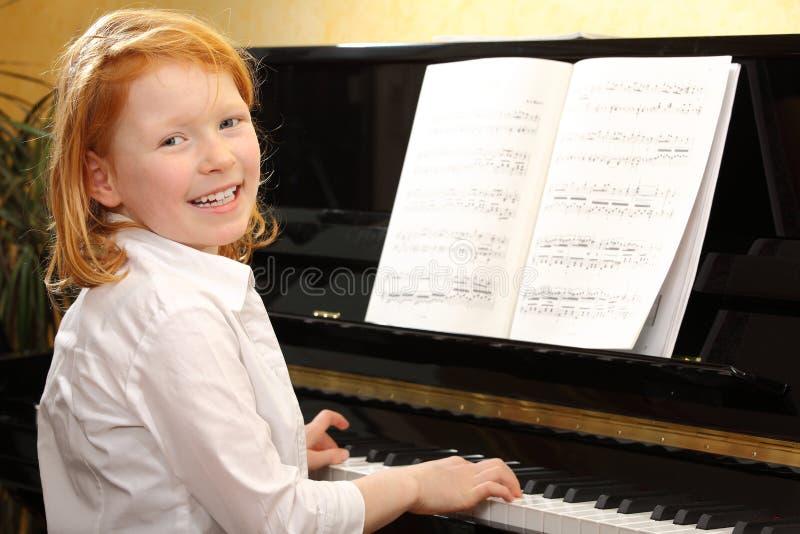 Girl plays piano stock photo