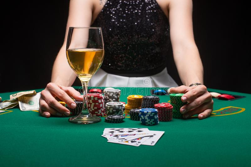 Girl plays poker in a casino, with chips, dollars, and wine. Concept of a gaming business.  royalty free stock photo