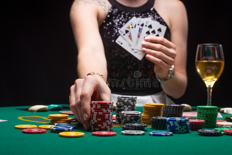 Girl plays poker in a casino, with chips, dollars, and wine. Concept of a gaming business.  stock images