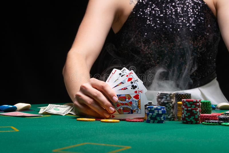 Girl plays poker in a casino, with chips, dollars, and wine. Concept of the gaming business. With space on a black background.  stock image