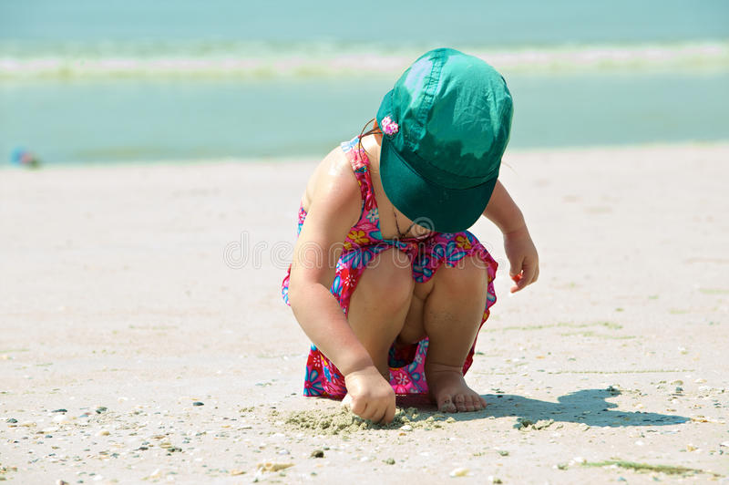 Girl plays on the sand stock images