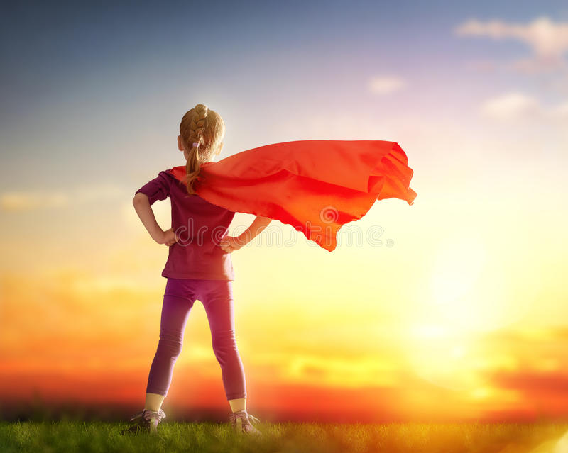 Girl plays superhero. Little child girl plays superhero. Child on the background of sunset sky. Girl power concept royalty free stock photo