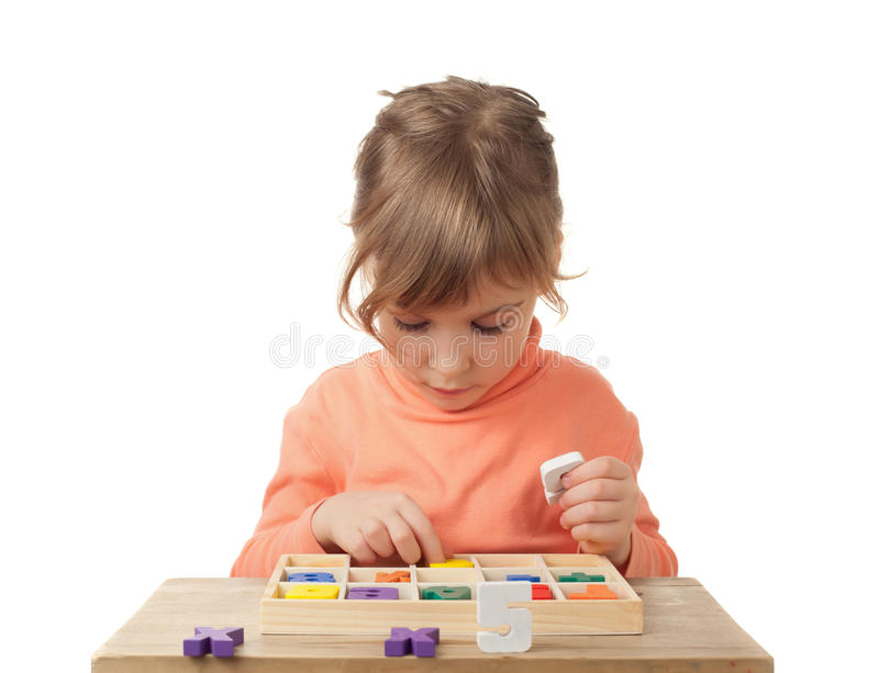 Girl plays in wooden figures in form of numerals stock photos