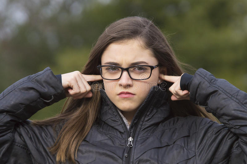 Girl plugging her ears. Young girl in glasses angrily plugging her ears royalty free stock photo