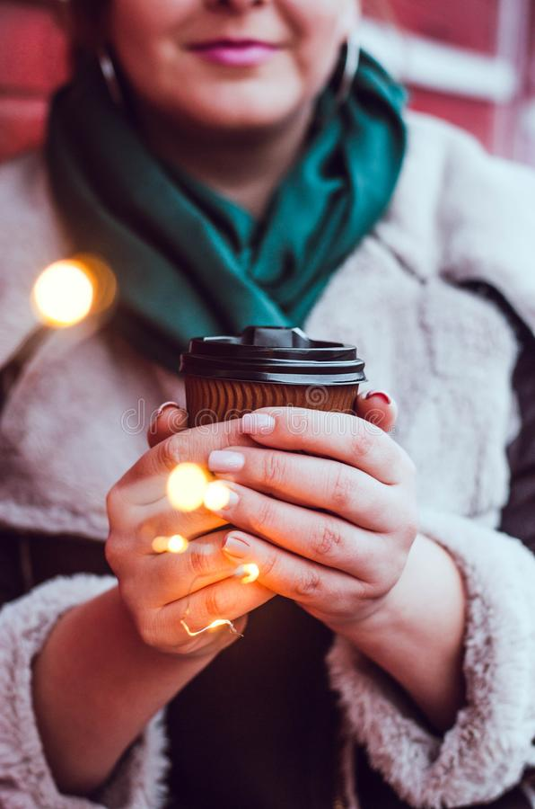 Girl plus size with a glass of coffee and a bright garland royalty free stock images