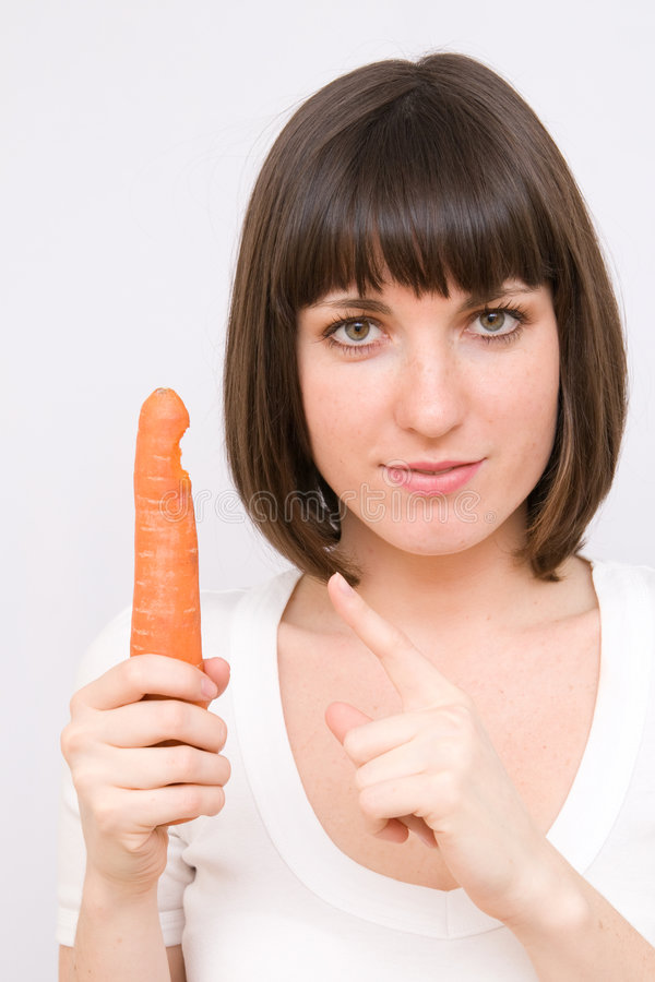 Girl pointing at carrot royalty free stock photography