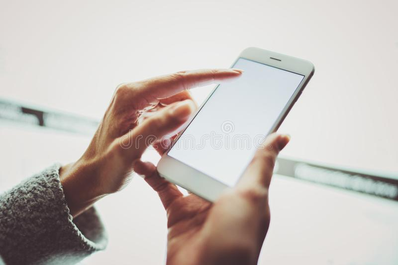 Girl pointing finger on screen smartphone.Female hands texting message mobile phone.Closeup on blurred light coloured royalty free stock images