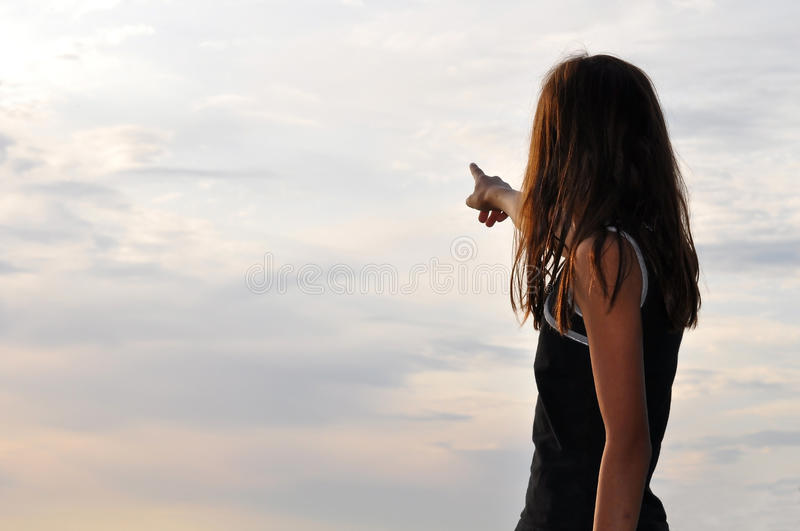 Girl pointing out to clouded sky