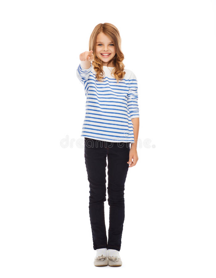 Girl pointing at you or imaginary screen. Education, school and gesture concept - cute little girl pointing at you or imaginary screen stock photography