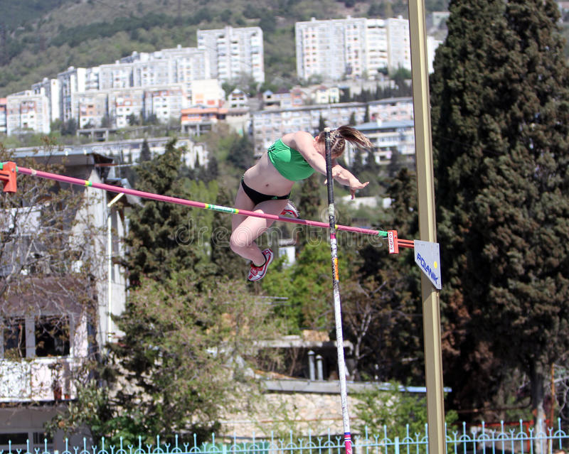 Girl on the pole vault competition stock image