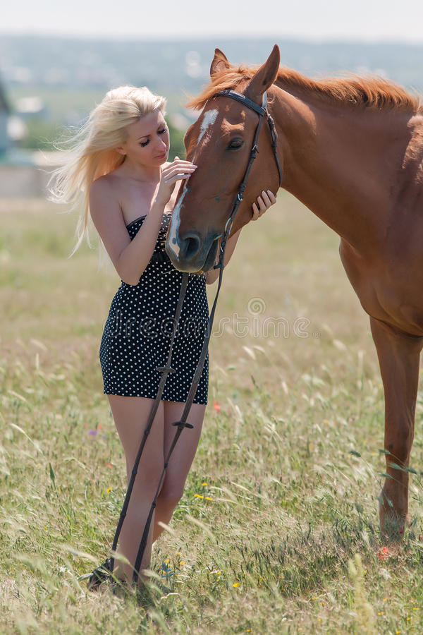 Girl in polka-dot dress with brown horse. Blonde woman stroking gelding. Young blonde woman in polka-dot dress with brown horse royalty free stock image