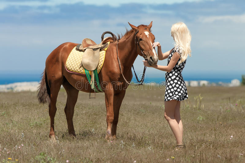 Girl in polka-dot dress with brown horse. Gelding and blonde woman. Young blonde woman in polka-dot dress with brown horse royalty free stock photography