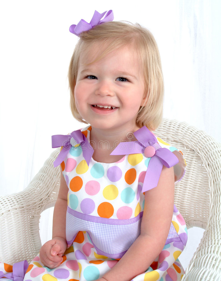 Girl in Polka Dot Dress on Chair. Closeup of smiling blond girl in colorful polka dot dress on wicker chair in front of white background royalty free stock photography
