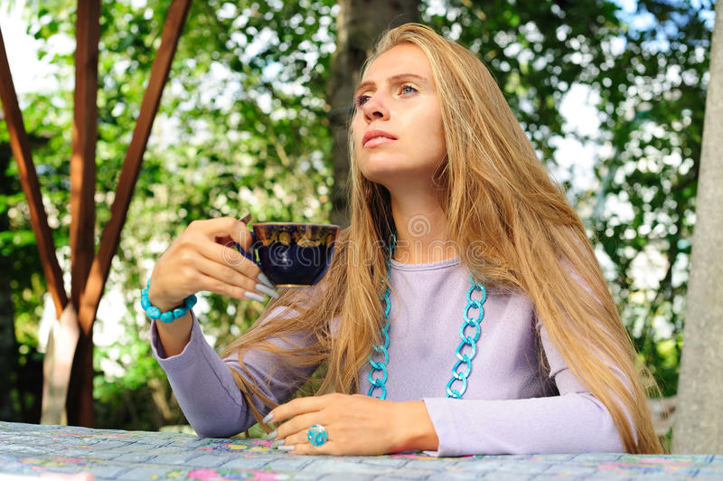 Girl pondering in the summer cafe royalty free stock image