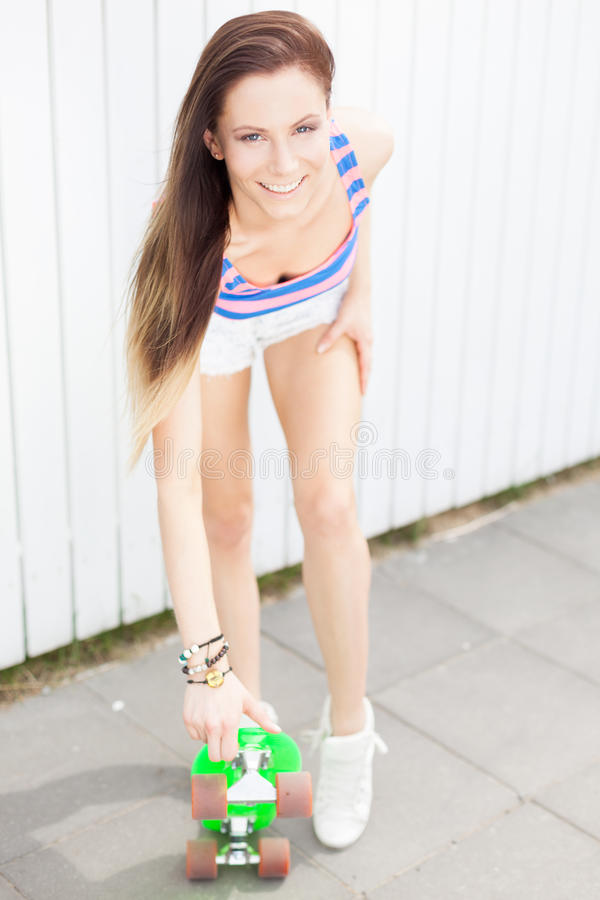 Girl with pony skateboard. Smiling girl with pony skateboard royalty free stock photo