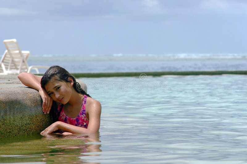 Girl in the pool. A girl in a pool with the ocean in the background stock photos