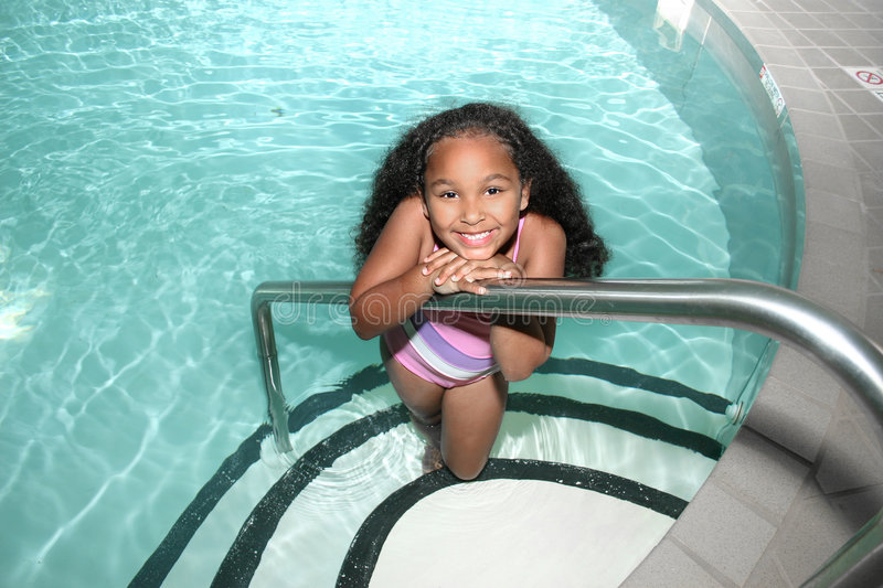 Girl in pool. Smiling African American girl posing on stairs in pool stock images