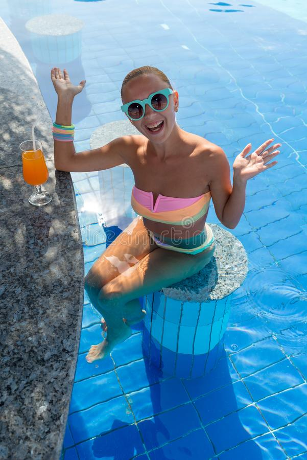 Girl in pool bar. At tropical tourist resort vacation destination stock image
