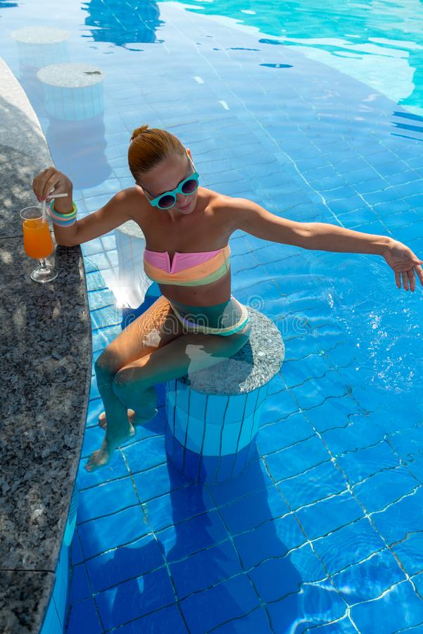 Girl in pool bar. At tropical tourist resort vacation destination royalty free stock image