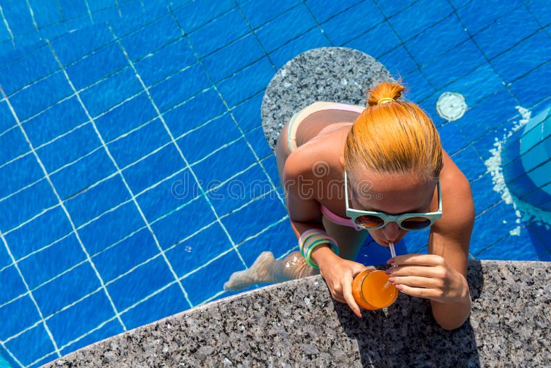 Girl in pool bar. At tropical tourist resort vacation destination stock photography