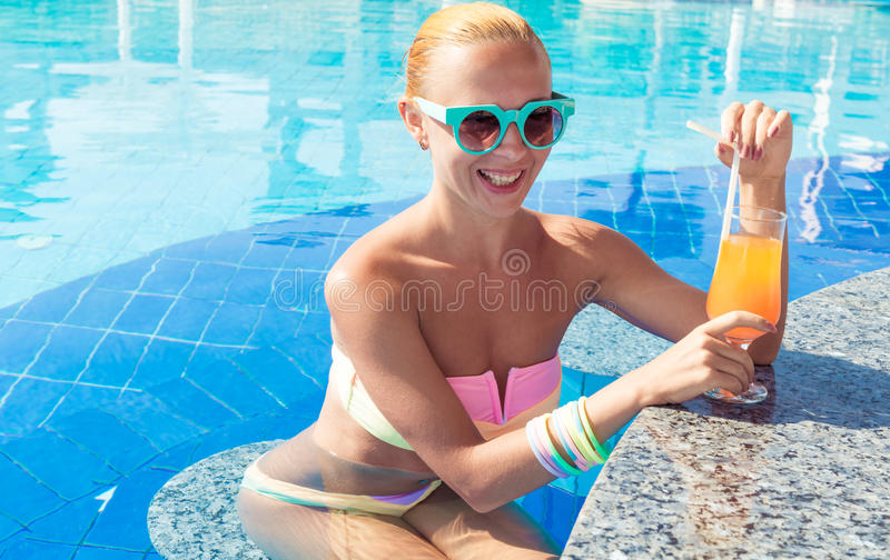 Girl in pool bar. At tropical tourist resort vacation destination stock photo