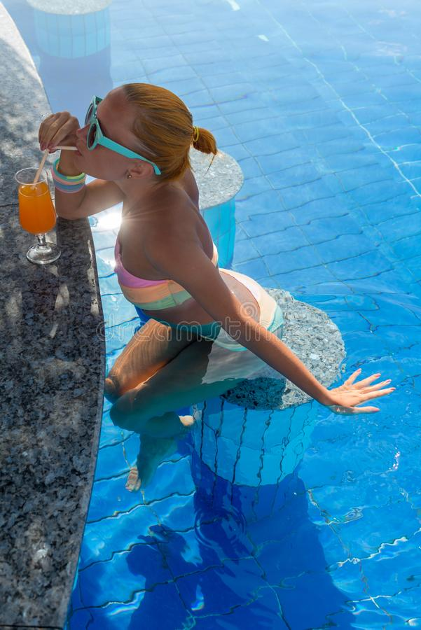 Girl in pool bar. At tropical tourist resort vacation destination royalty free stock photography