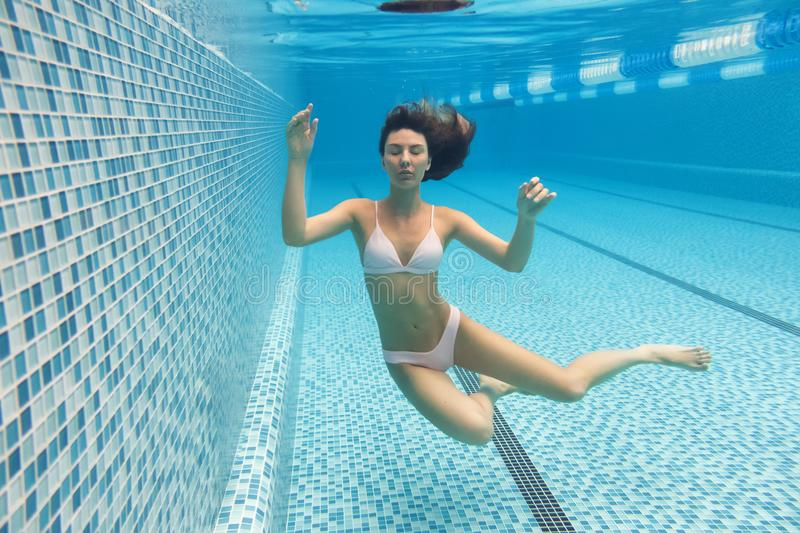 Girl in the pool. She dives into the pool. Under water in a pink bathing suit stock photos