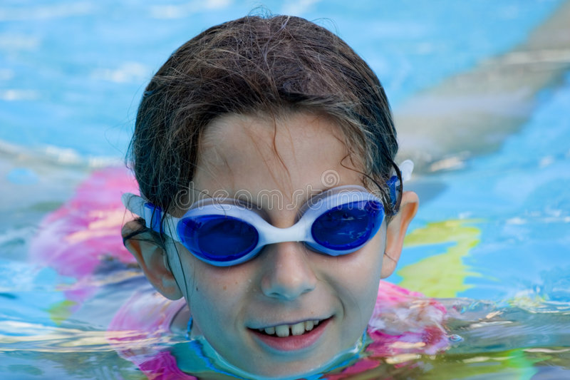 Girl in pool with goggles. Colourful reflections in the water, intense blue goggles and pool water stock photography