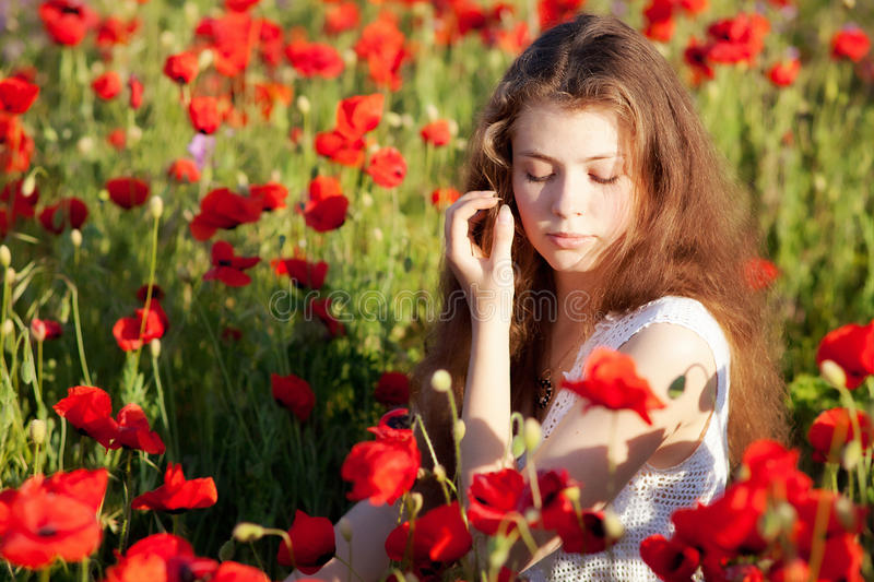 Girl on a poppy field stock images