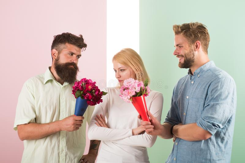 Girl popular receive lot men attention. Men competitors with bouquets flowers try conquer girl. Girl likes to be in stock images