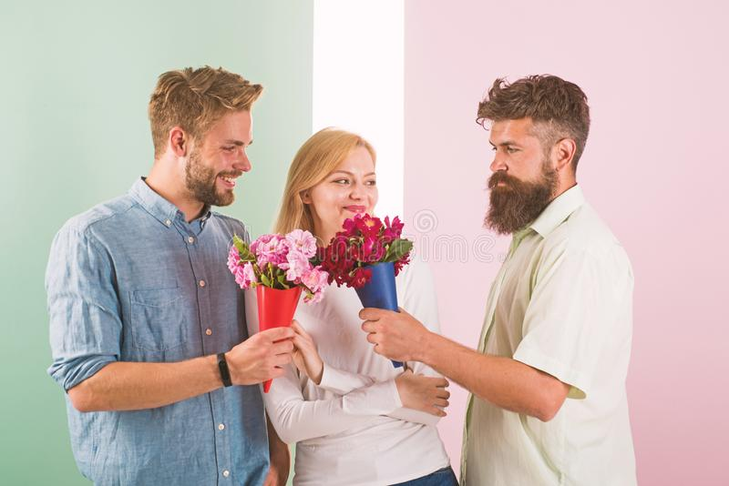 Girl popular receive lot men attention. Men competitors with bouquets flowers try conquer girl. Love triangle. Woman. Smiling has opportunity choose partner stock photos