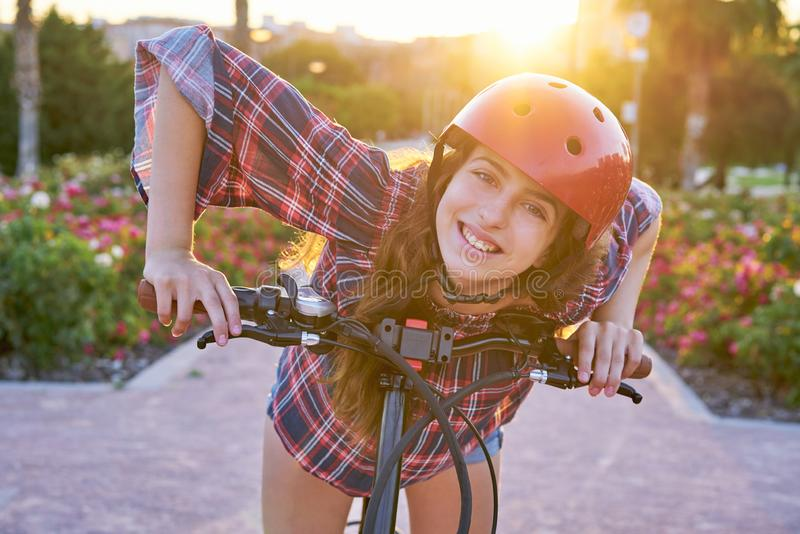 Girl portrait on bicycle with helmet smiling. Happy at the flowers park outdoor royalty free stock image