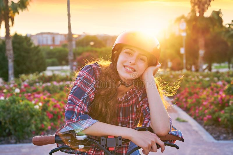 Girl portrait on bicycle with helmet smiling. Happy at the flowers park outdoor royalty free stock photos
