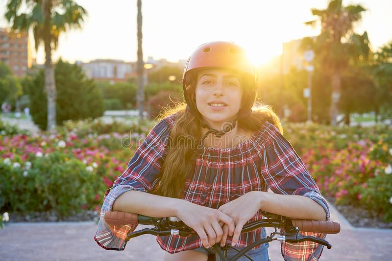 Girl portrait on bicycle with helmet smiling. Happy at the flowers park outdoor stock photography