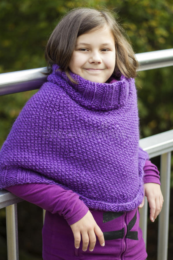 The girl. The portrait of a teenage girl wearing purple poncho royalty free stock photography