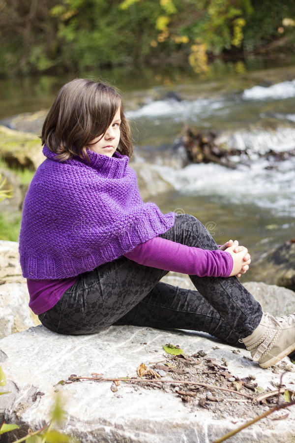 The girl. The portrait of a teenage girl wearing purple poncho stock photo