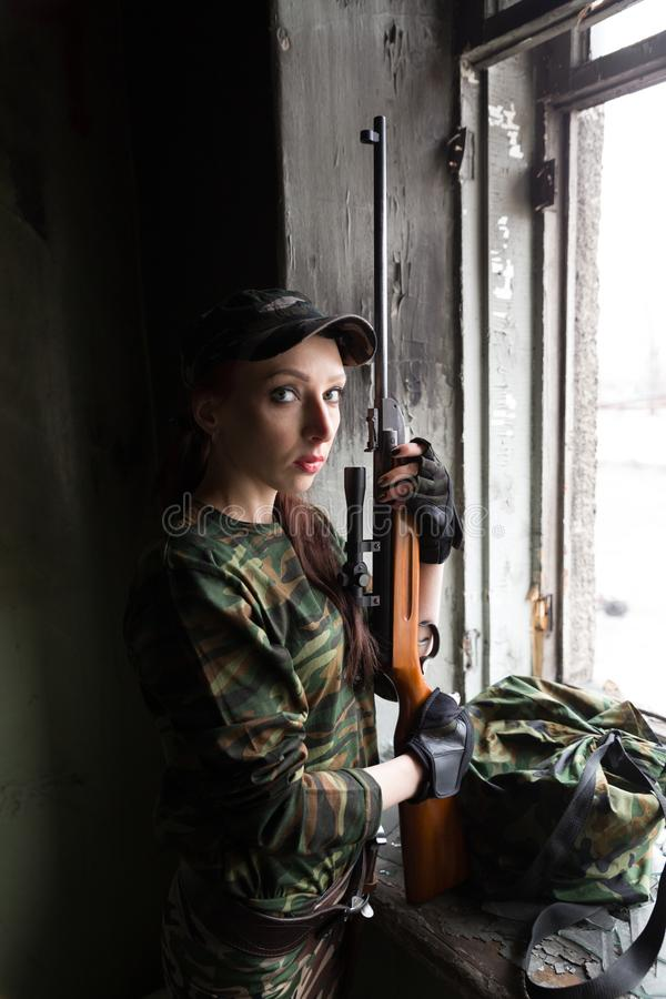 A thin red-haired girl stands at the broken window with a rifle. The girl in green camouflage with a gun. Military service for. The girl portrays a soldier royalty free stock image