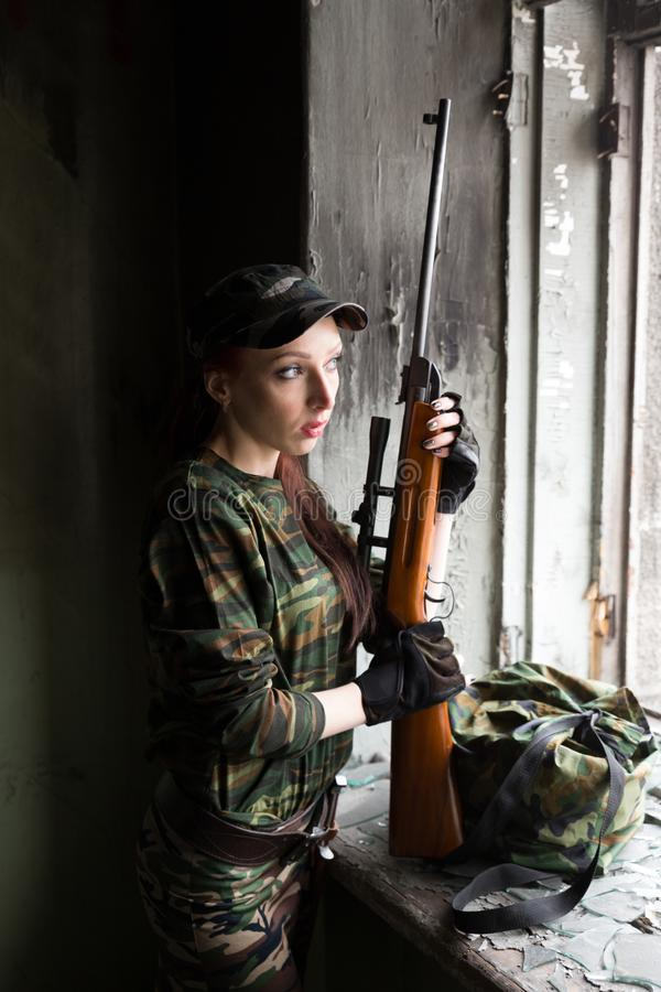 A thin red-haired girl stands at the broken window with a rifle. The girl in green camouflage with a gun. Military service for. The girl portrays a soldier stock photography