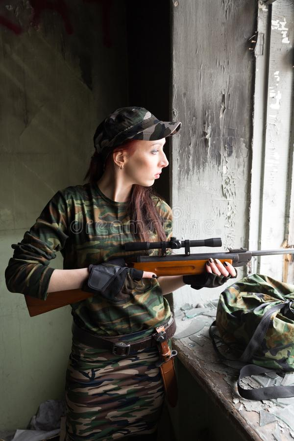 A thin red-haired girl stands at the broken window with a rifle. The girl in green camouflage with a gun. Military service for. The girl portrays a soldier royalty free stock photos