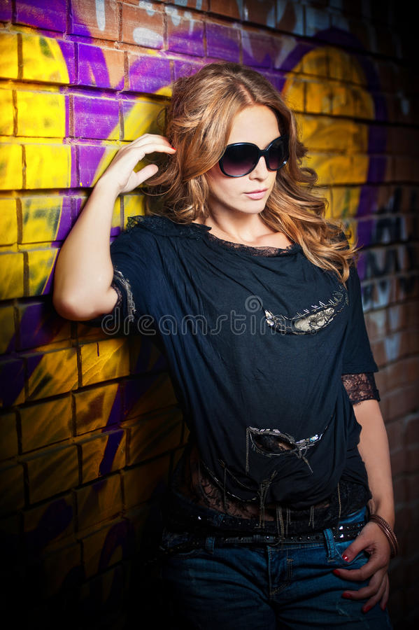 Girl posing fashion near red brick wall on the street royalty free stock image