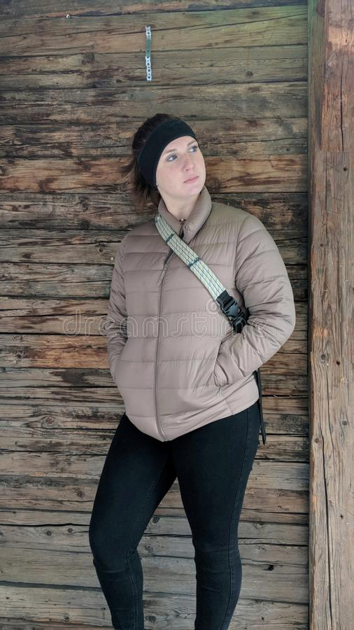 Girl posing in front of wood wall in Winter wearing a jacket. stock photography