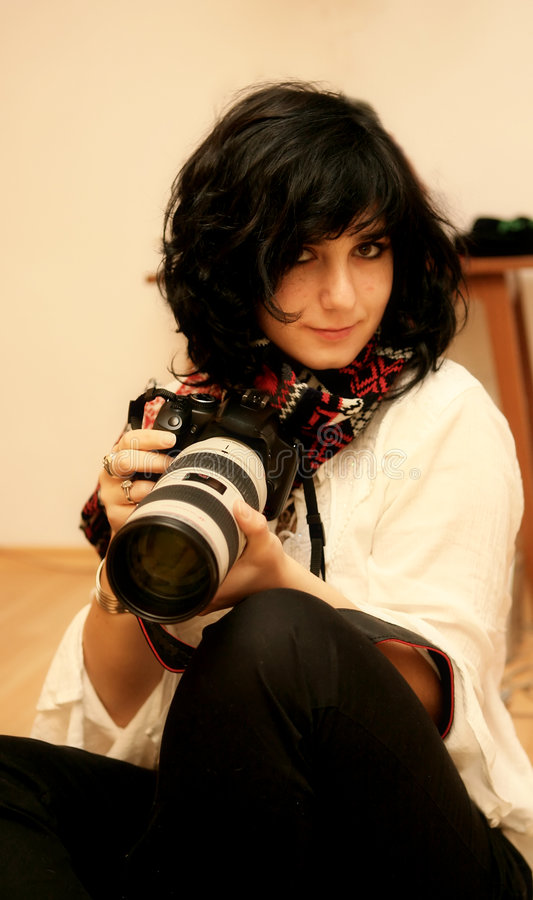 Girl posing with her camera. Beautiful girl smiling and taking pictures royalty free stock photos