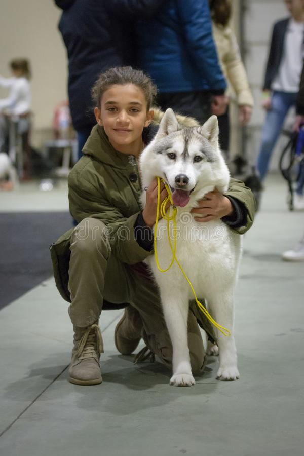 Girl posing with her Siberian Husky puppy before parading in the contest royalty free stock photos