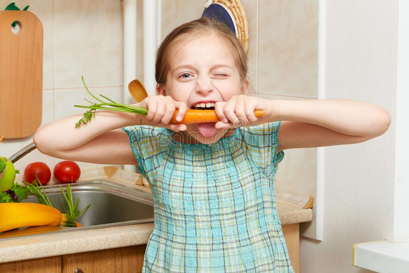 Girl posing in home kitchen with fresh fruits and vegetables, eating a carrot - healthy eating concept stock photos