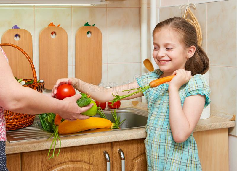 Girl posing in home kitchen with fresh fruits and vegetables - healthy eating concept stock photo