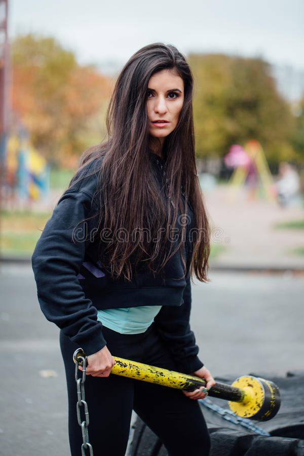 Girl posing at park with hammer and tractor tire. Beautiful brunette sportsgirl workout with sledgehammer. Fitness concept and functional training stock photography